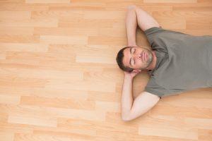 A man lying on a wooden floor