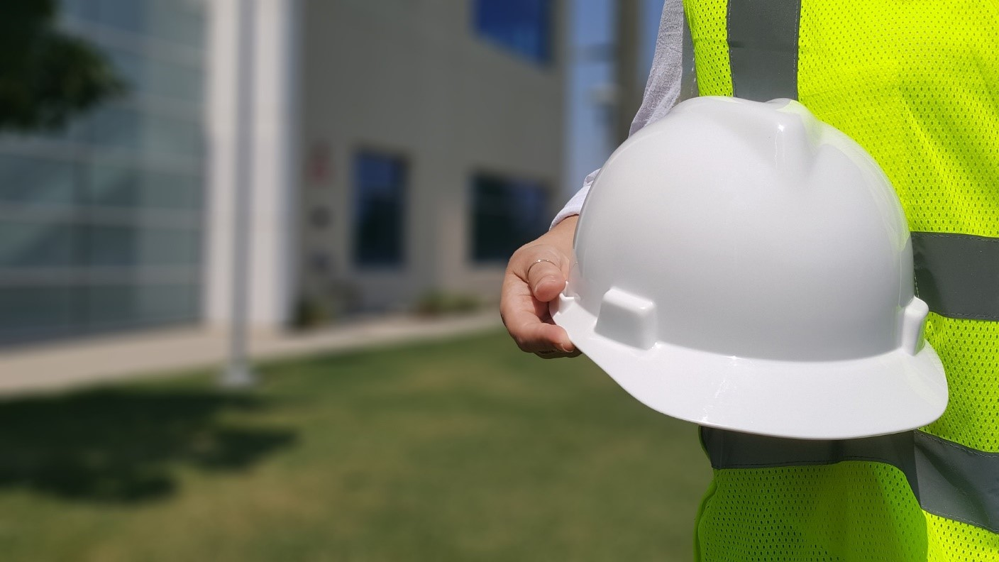 A contractor holding a hard hat